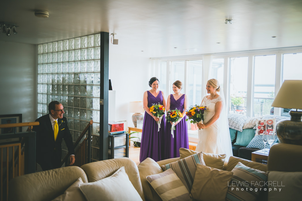 father of the bride sees bride and bridesmaids