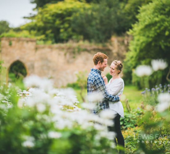 Ogmore pre-wedding photoshoot Ogmore wedding couple hold and kiss in front of daisies