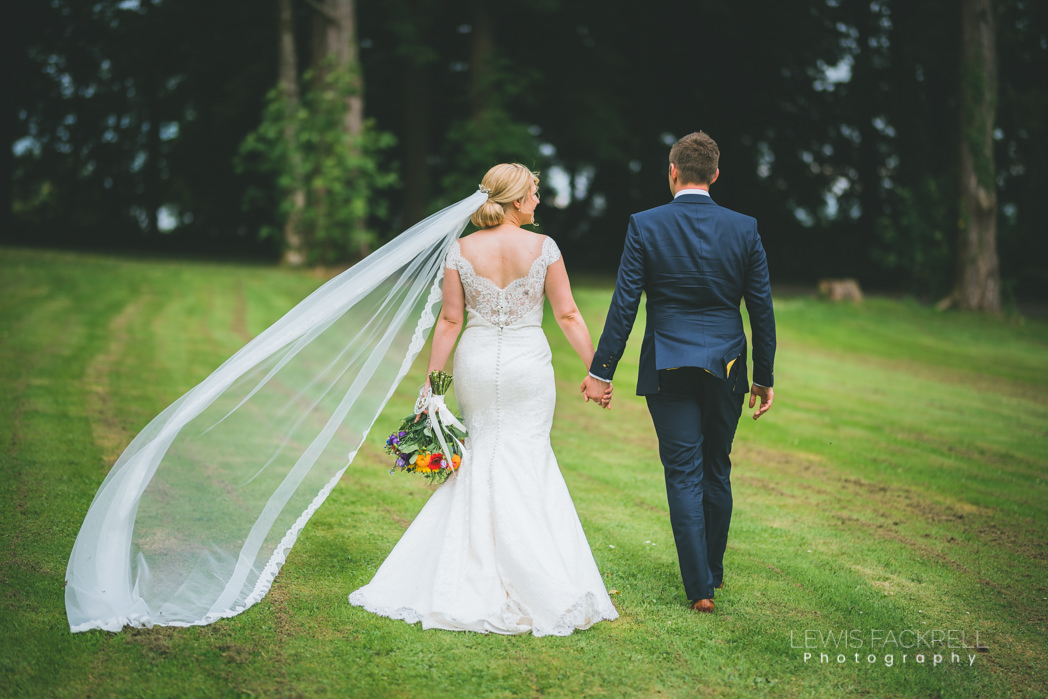 veil caught by the wind as couple walks