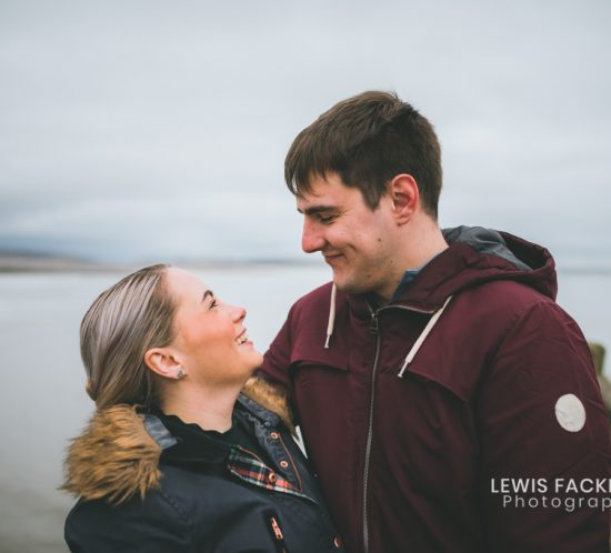 Engagement photo session with couple holding each other smiling