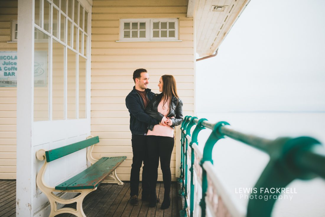 Penarth pre-wedding photography session with couple cuddling on pier