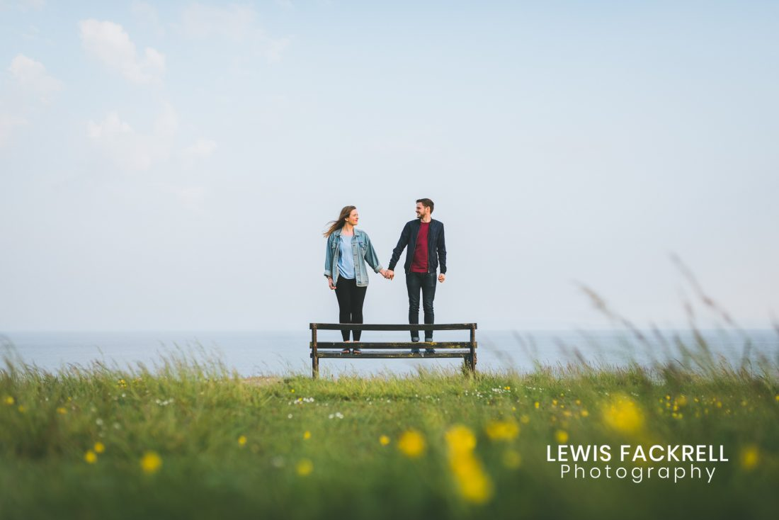 barry island pre-wedding photo session of couple stood on bench