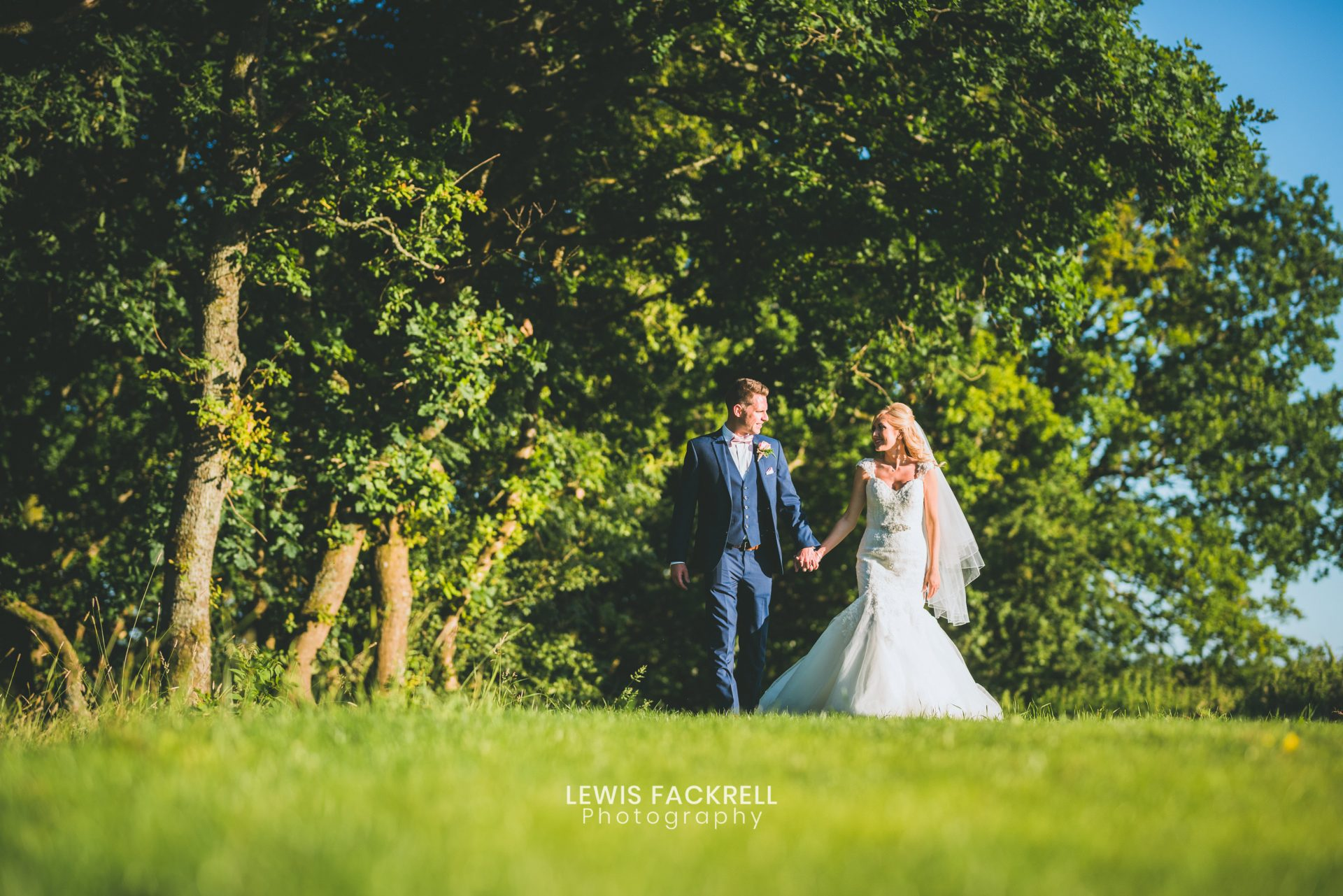canada lodge, cardiff wedding photography of couple walking along the tree line at the venue holding hands