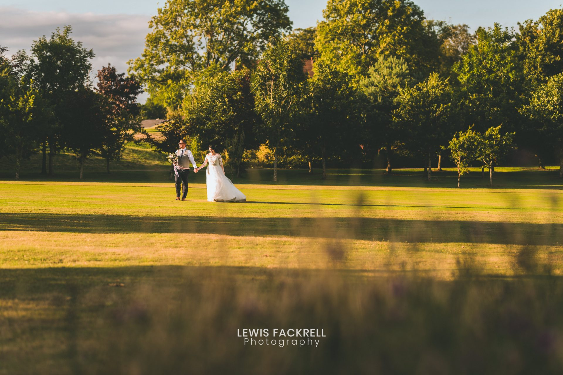 Cottrell park wedding of bride and groom as they walk on the lawn in the summer evening light