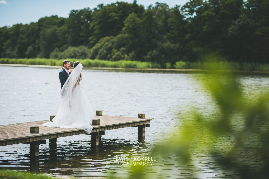 Hensol Castle Wedding photography of bride and groom stood on jetty at venue