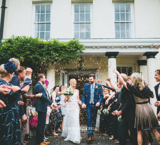 Plas Glansevin Wedding photographer with Rhi & Ollie walking out to confetti
