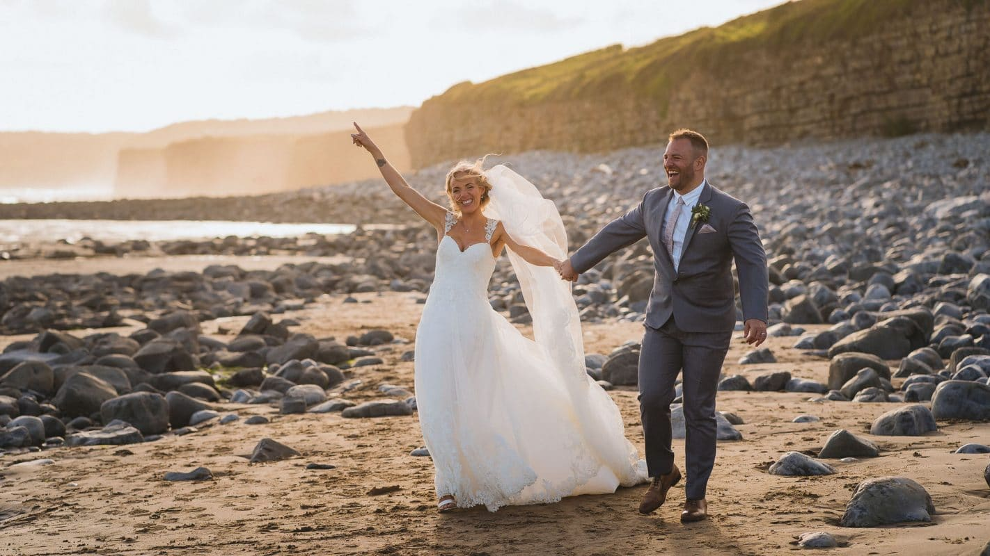 bride and groom walking along beach at Rosedew farm