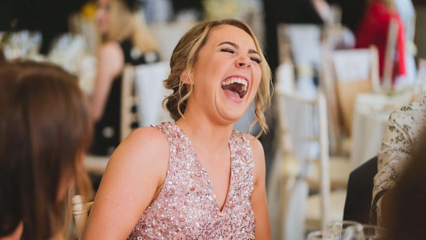 bridesmaid laughing uncontrollably.