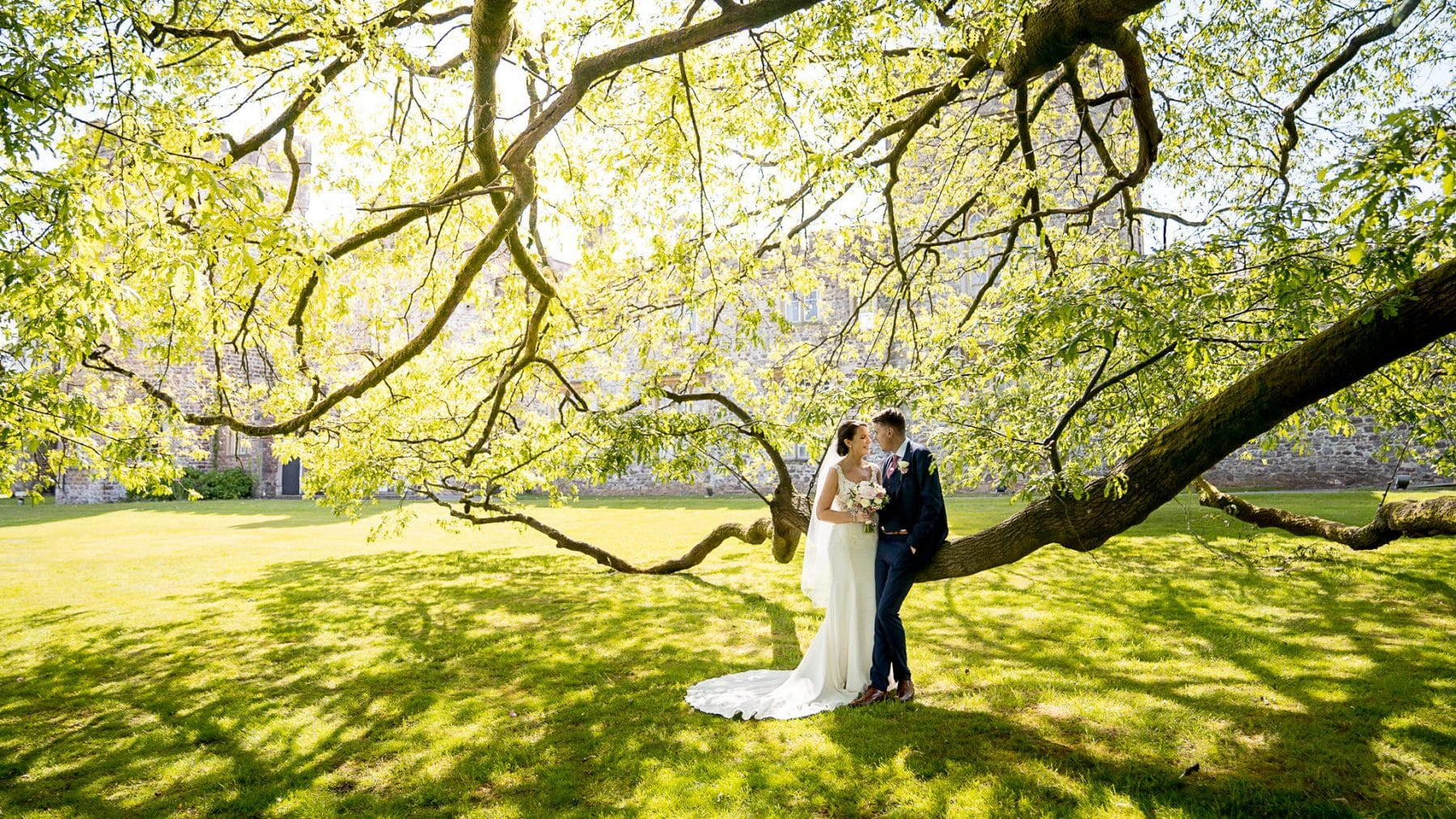 Hensol Castle wedding photography in South Wales of bride and groom kissing under a tree